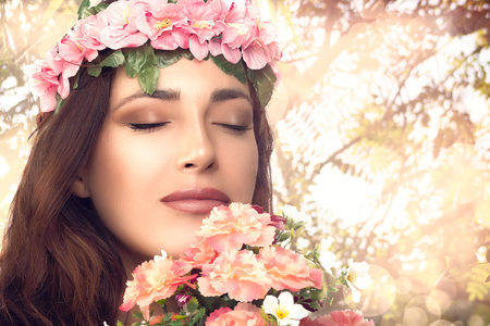 Beauty Spring Girl Enjoying Nature. Fashion Model Woman with Floral Ring on Head Smelling a Bouquet of Flowers with Eyes Closed. Portrait with Copy Space for Text