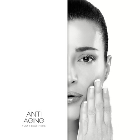 aging face: Anti Aging and skincare concept with a monochrome half face portrait of a serene young woman with her manicured nails raised to her cheek and a flawless smooth complexion with copyspace alongside. Template design with sample text