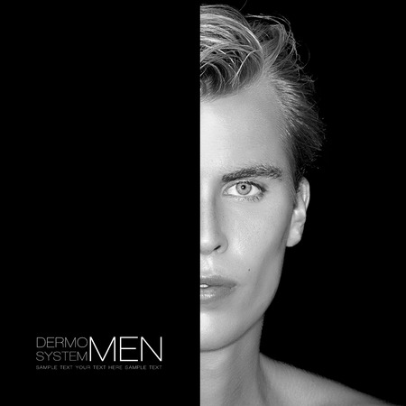 Handsome young man half face. Perfect skin. Men skincare concept. Monochrome Portrait isolated on black. Template design with sample text Stockfoto