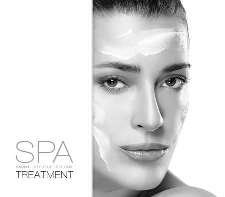 Spa treatment and beauty concept. Portrait of a gorgeous woman with cosmetic cream on her cheeks and forehead and blank copyspace alongside with sample text. Template design