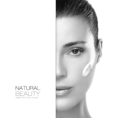 elasticidad: Concepto de la belleza con un retrato de medio rostro de una mujer hermosa con una piel limpia y sana y crema cosmética en la mejilla. Tratamiento de Spa. Diseño de la plantilla con texto de ejemplo