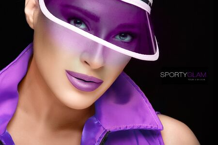 Sporty beauty. Fashiopn Model GIrl in Purple Sun Visor and Violet Collared Shirt, Looking at Camera. Sporty Glam Concept. Isolated on Black Background with Sample Text