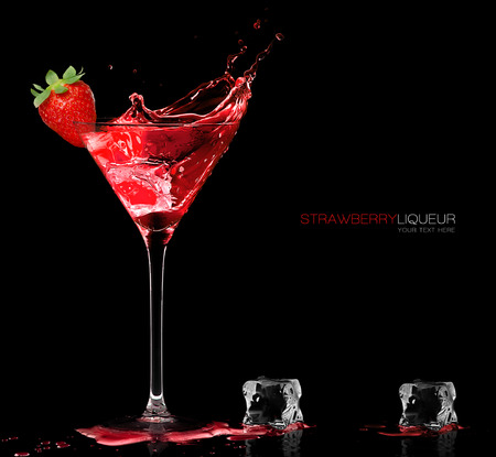Stylish cocktail glass with red liquor splashing out, garnished with a ripe fresh strawberry, closeup isolated on black with sample text.