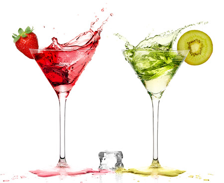 abstract liquor: Two stylish cocktail glasses with fruity liquor splashing out, garnished with a ripe fresh strawberry and kiwi, closeup isolated on white. Party concept. Stock Photo