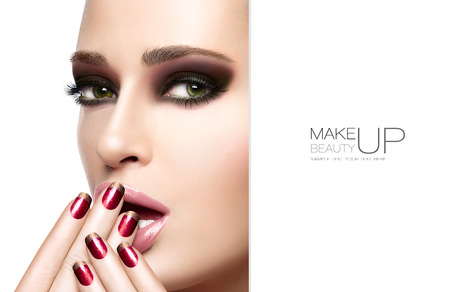 nail lacquer: Beautiful young woman with hands on her face covering her mouth. Perfect skin. Nail art and makeup concept. Autumn winter trendy make-up. High fashion Portrait isolated on white. Template design with sample text
