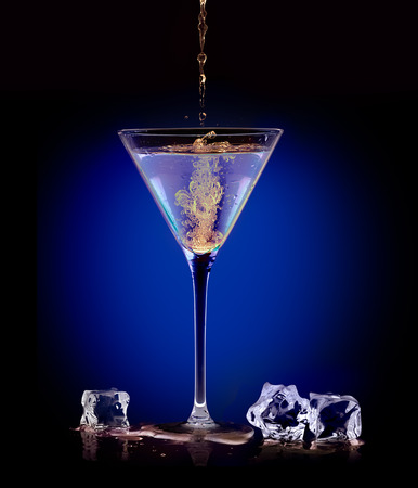 flanked: Dramatic image on dark blue of the mixing and blending of two alcoholic beverages when pouring a mixer into a martini in a conical glass flanked by ice cubes. Party concept Stock Photo