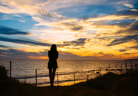 seaside: Silhouette of a Pensive Woman Standing at the Beach and Facing at the Peaceful Ocean During Sunset Time.