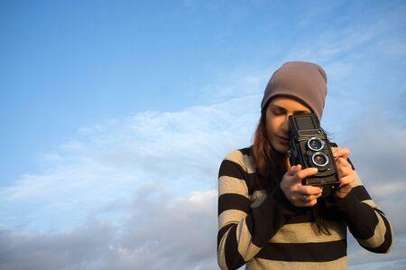 grabado antiguo: Bastante joven mujer tomando fotos usando una c�mara de la vendimia al aire libre. Retrato estilo de vida sobre el cielo azul con copia espacio a la izquierda.