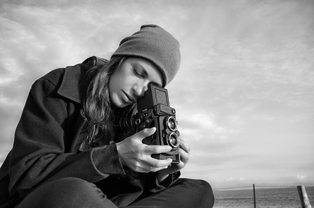 vintage photo: Young Female Photographer Taking Ocean Scenery Using Vintage Camera, Captured in Monochrome Color. Stock Photo