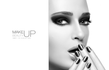 Beauty and Makeup concept with Beautiful young woman with hands on her face covering mouth. Perfect skin. Trendy nail art and smoky eyes. Close up monochrome portrait isolated on white. Template design with sample text