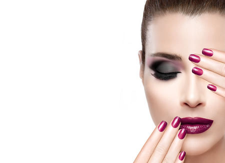 cosmetic lacquer: Beauty and Makeup concept. Beautiful fashion model woman with hands on face covering half mouth and one eye. Perfect skin. Professional manicure and makeup. smoky eyes. Fashionable eyelashes. High fashion portrait isolated on white with copy space for tex Stock Photo