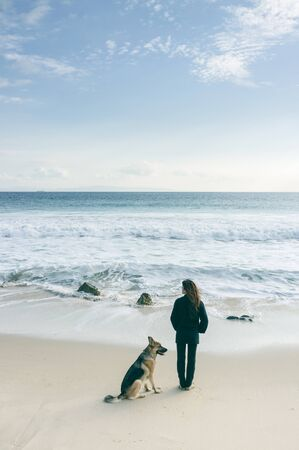 german ocean: Rear view of a woman standing on a beach looking out over the ocean with her German Shepherd dog alongside her Stock Photo