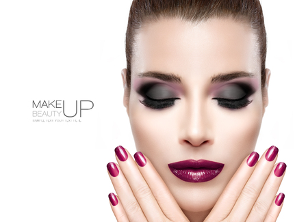 Nail art and Makeup concept. Beautiful fashion model woman face with eyes closed. Perfect skin. Trendy burgundy lips, nails and smoky eyes. Fashionable eyelashes. High fashion portrait isolated on white with sample text Stockfoto