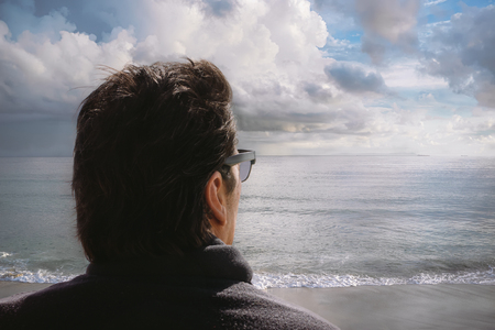 head in the sand: Back man head. Dark-haired man with black sunglasses and turtleneck sweater looks to the horizon from an Atlantic beach. Closeup portrait outdoors with copy space at the right.