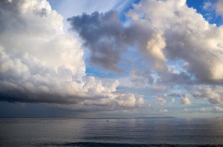 storm background: After storm. Seascape with towering white cumulonimbus clouds in a blue sky above a calm ocean, environmental, weather or nature background. Stock Photo