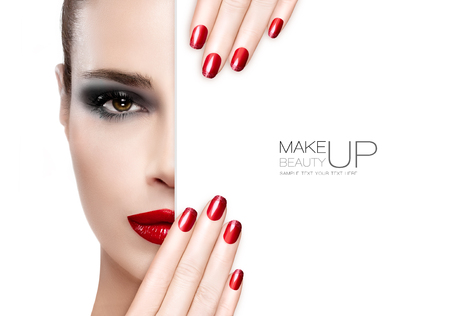 makeup fashion: Beauty Makeup and Nai Art Concept. Beautiful fashion model woman with smoky eye makeup, foundation on a unblemished skin and trendy red lipstick to match her manicured nails, half face with a white card template. High fashion portrait isolated on white