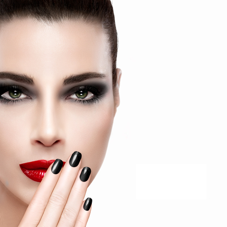 winter fashion: Beauty and Makeup concept. Beautiful fashion model woman with trendy red lips and black smoky eyes. Long eyelashes. Black nail art. High fashion portrait isolated on white with copy space at the right