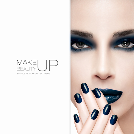 Gorgeous beauty fashion model wearing dark smoky eye makeup with matching dark lipstick and nail lacquer on her manicured nails which are raised to her lips, closeup part face with white card template