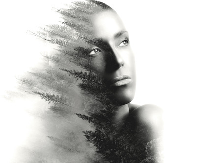 Double exposure portrait of a beautiful young woman and forest. Monochrome portrait over white background with copy space at the right.