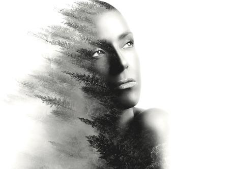 exposicion: retrato de la doble exposición de una mujer joven y bella y el bosque. Retrato monocromático sobre el fondo blanco, con copia espacio a la derecha. Foto de archivo