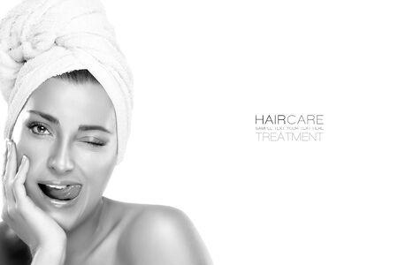 Haarverzorging en schoonheid concept. Close-up van het gezicht van een jonge vrouw met haar haar vastgebonden in een handdoek, blote schouders een grappige uitdrukking zijn tong uitsteekt. Monochroom afgezwakt portret geïsoleerd met voorbeeldtekst