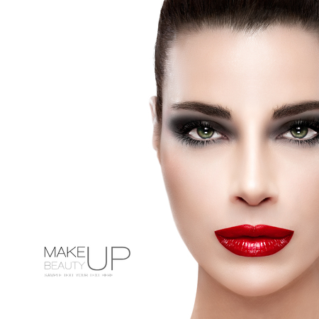Beauty and Makeup concept. Beautiful fashion model woman with bright make-up. Perfect skin, trendy red lips and black smoky eyes with long eyelashes. High fashion portrait isolated on white with sample text at the left