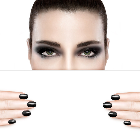 Dark smoky beauty and nail art concept with a woman wearing creative dark eye makeup holding a blank white card template covering her mouth with matching dark manicured nails. Portrait isolated on white with copy space for text. Stockfoto