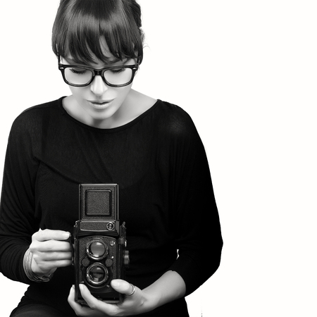 modelos negras: Mujer joven atractiva que desgasta la ropa negra y vidrios Captura de fotos Utilizando la c�mara de la vendimia. Monocromo retrato aislado en fondo blanco con copia espacio para texto