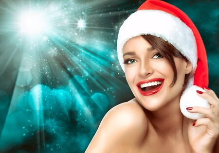 winter fashion: Gorgeous woman wearing vivid red lipstick and a festive red Christmas Santa hat laughing at the camera against a colorful blue starburst with sparkling bokeh. Christmas concept