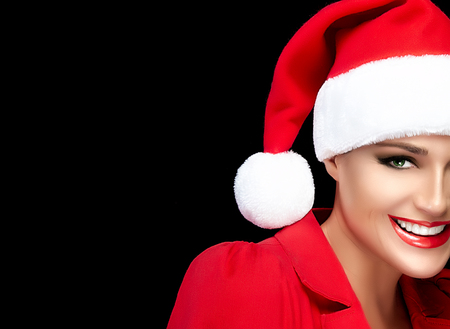 Joyful Christmas girl in a festive red Santa Hat and matching top looking at the camera with a lovely warm friendly smile, half face portrait isolated on black with copy space for text. Happy people.