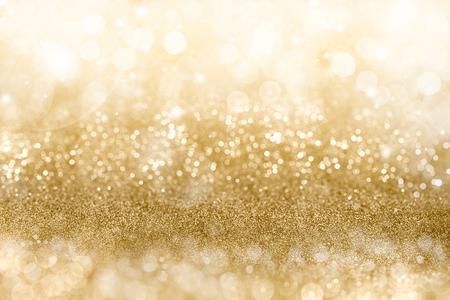 Sfondo dorato di Natale con bande graduati di diversa bokeh frizzante e scintillanti di luci della festa e glitter, copyspace full frame per il messaggio di saluto di stagione