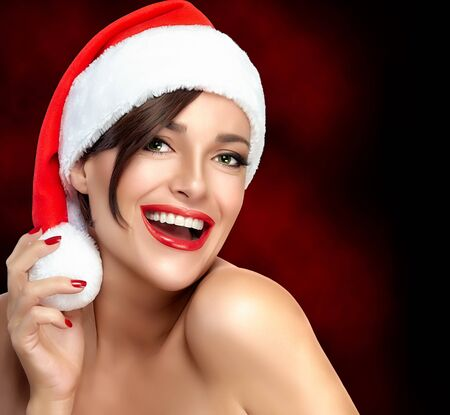 labios sexy: Chica sexy vivaz en un sombrero de Santa que celebra la Navidad y la temporada festiva riendo a la cámara con los labios rojos de moda y manicura, los hombros desnudos, cerca cabeza y hombros ver con copia espacio para el texto Foto de archivo
