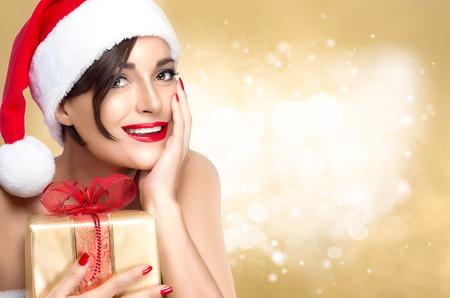 Prachtige Miss Kerstman in een feestelijke rode hoed met een gouden kerstcadeau greep naar haar borst met haar hand op haar wang lachend naar de camera, over gouden glitter onscherpe achtergrond met copyspace voor tekst