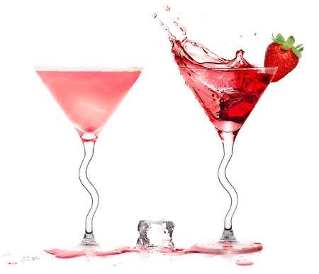 cocktail glasses: Two stylish cocktail glasses with fruity liquor splashing out, garnished with a ripe fresh strawberry and sugar, closeup isolated on white. Party concept.