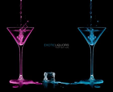 coctel de frutas: El cubo de hielo entre dos copas de cóctel llenas de color azul y rosa alcohólico licor exótico salpica hacia fuera, con copia espacio en negro, el concepto de estilo y celebración. Diseño de la plantilla con texto de ejemplo Foto de archivo