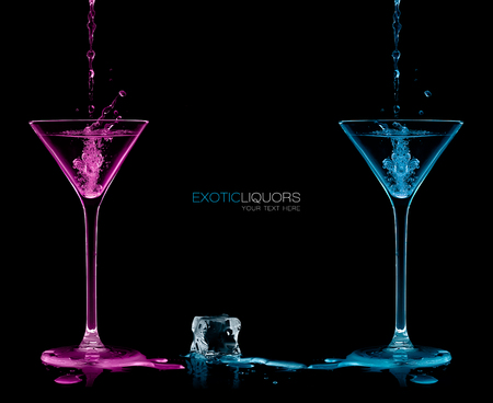 Ice cube between two cocktail glasses filled with blue and pink alcoholic exotic liqueur splashing out, with copy space on black, concept of style and celebration. Template design with sample text Фото со стока