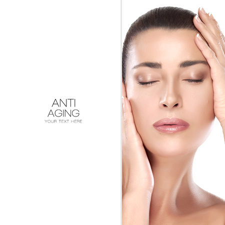 beautiful face woman: Beautiful young woman with hands raised to her face and closed eyes with a serene expression suitable for skincare and spa concepts. Perfect skin. Beauty portrait isolated on white with copyspace alongside. Template design with sample text Stock Photo