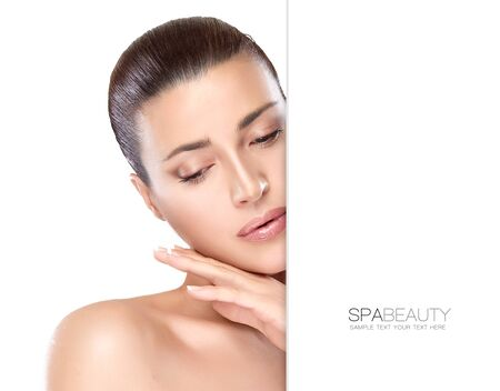 caresses: Beauty portrait of a gorgeous natural young woman with perfect healthy skin and bare shoulders caressing her face with a serene expression, suitable for skincare and spa concepts, isolated on white with copyspace alongside. Template design with sample tex Stock Photo