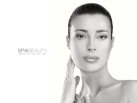 revitalizing: Head and shoulders beauty portrait of a gorgeous natural young woman looking at the camera with a serene expression suitable for skincare and spa concepts. Monochrome portrait isolated on white with sample text