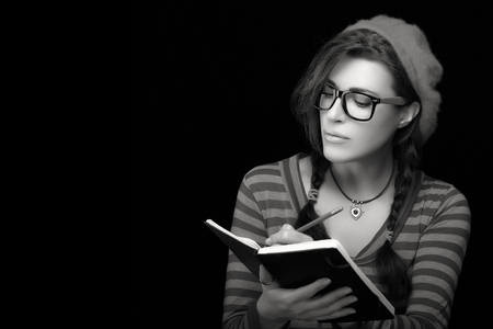 Close up beautiful college girl in trendy outfit writing on her notebook. Monochrome portrait isolated on black background with copy space for text Standard-Bild
