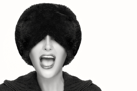 facial gestures: Winter beauty fashion. Close up monochrome portrait of pretty young woman with open mouth facial expression, wearing trendy fur hat that covers his eyes. Gestures and grimaces. Portrait isolated with copy space for text. Stock Photo