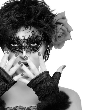 black lady: Carnival concept with a short hair gorgeous woman wearing elegant black mask and big rose flower on her left ear. Monochrome close up portrait isolated on white background with copy space for text.