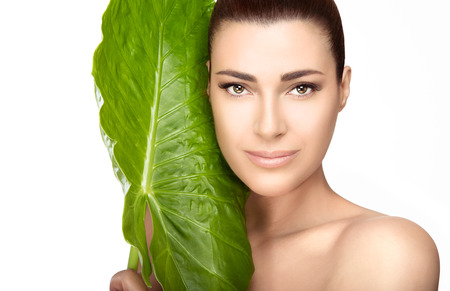 Beauty and skincare portrait. Beautiful spa girl with the large fresh green leaf of a tropical plant against her cheek as she looks at the camera with a gentle smile in a spa and wellness concept