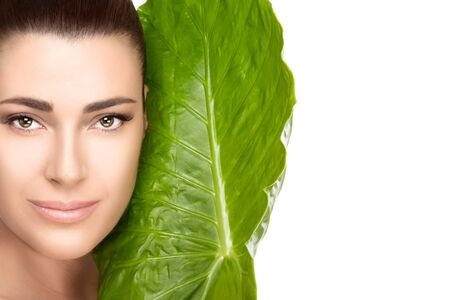 fresh leaf: Beauty and skincare portrait. Beautiful spa woman face with the large fresh green leaf of a tropical plant against her cheek as she looks at camera with a gentle smile in a spa and wellness concept. isolated on white Stock Photo