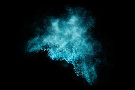 青い粉塵粒子の爆発が黒雪や花火の効果に似ています。黒に分離された色の爆発のクローズ アップ