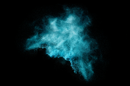 Blue dust particle explosion resembling snow or a pyrotechnic effect over black. Closeup of a color explosion isolated on black