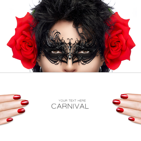 cosmetic lacquer: Masquerade. Beautiful fashion model woman with elegant black mask and big red rose flowers on her ears to match her manicured nails, holding a white card template covering her mouth. Beauty and makeup concept. High fashion portrait isolated on white with