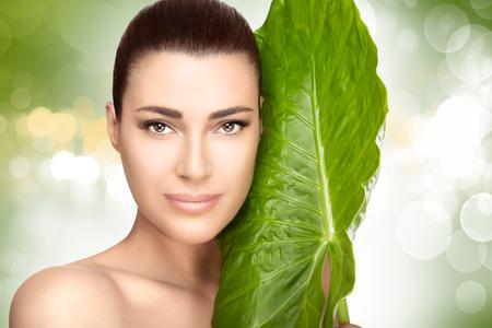 Portret piękno atrakcyjnej naturalnym młoda dziewczyna z dużym świeżych zielonych liści, która odbyła się na jej policzku przeciwko miękkich zielone tło bokeh w spa i wellness koncepcji