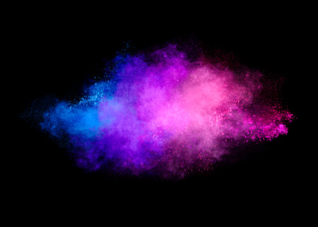 Colorful dust particle explosion resembling a pyrotechnic effect. Closeup of a color explosion isolated on black 스톡 콘텐츠