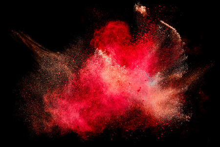 Colorful dust particle explosion resembling blood or a pyrotechnic effect over black. Closeup of a color explosion isolated on black Foto de archivo